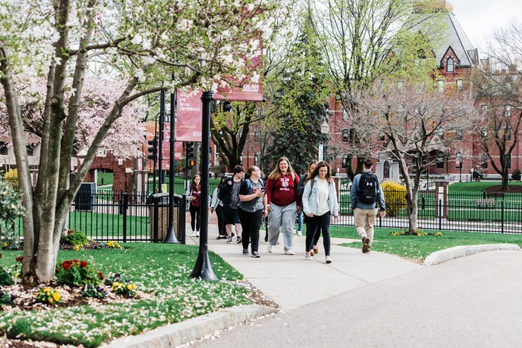 dean college students walking through campus on a spring day with flowers in bloom.