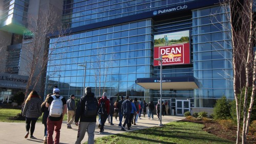Dean College student standing behind a podium reading the Autobiography of Benjamin Franklin at the Franklin Public Library.