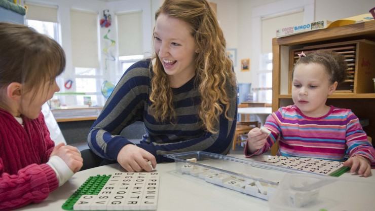 A student plays a word game with two children in the Children's Center