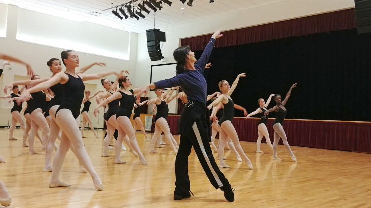 A dance professor leads a group of ballet students during a class.