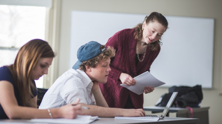 A student looks over a student's shoulder to help with classwork in a Dean College classroom