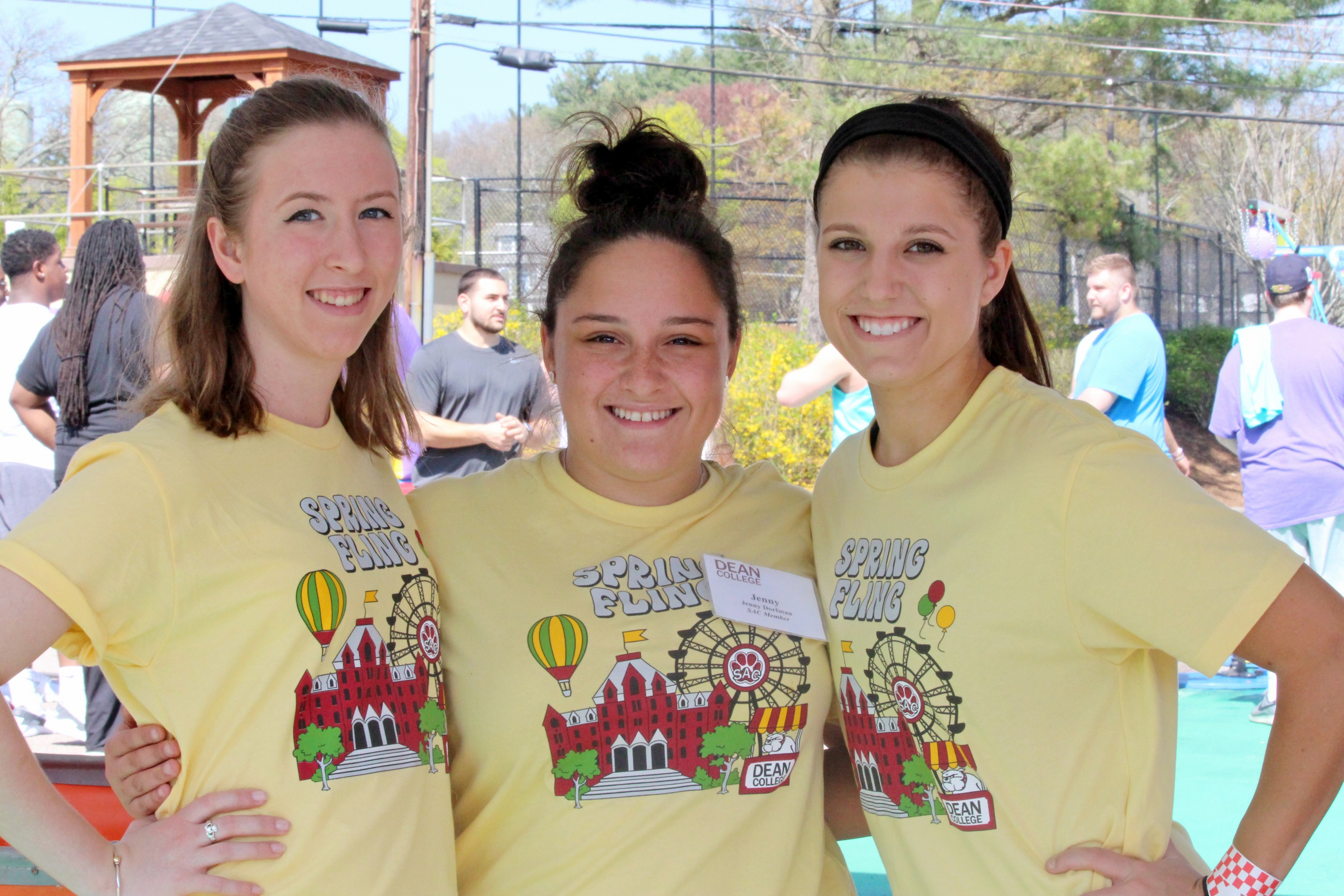 three students smiling at the camera, each wearing dean college club t-shirts